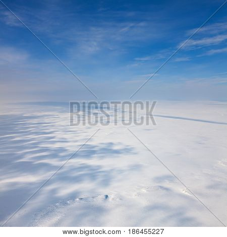 Aerial view above the snow-covered space of endless tundra in time of cloudy winter day.