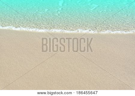 Soft wave of blue ocean on sandy beach. Background / Sand and wave at the beach background. Drop space on bottom for text and other.