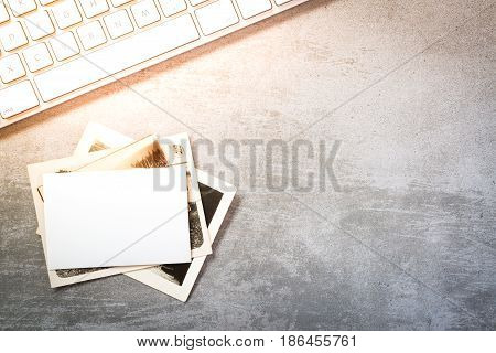 Vintage photos and computer keyboard on concrete background