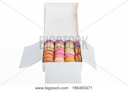 Colorful macaroons in a gift box isolated on white background. Sweet macarons. Top view with copy space
