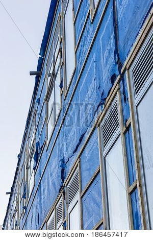 Poole England - December 2014: Construction Site wrapped by blue waterproof membrane sheets