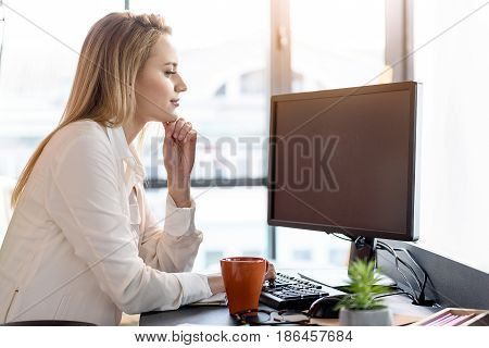 Working with pleasure. Confident woman enjoying her work. She is sitting at table concentrating on her computer against window