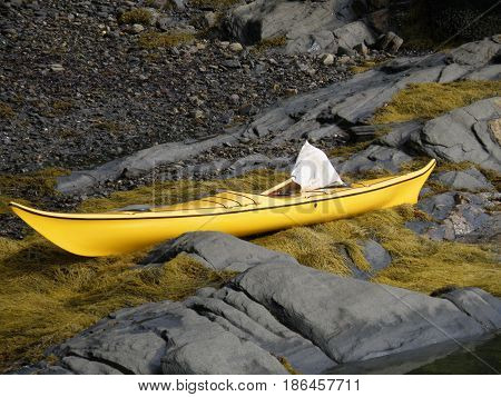 Yellow kayak sitting on rocks and seaweed in Casco Bay Maine.