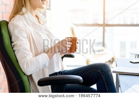 Need break. Young hardworking woman sitting in office and drinking coffee with smile. Window in the background