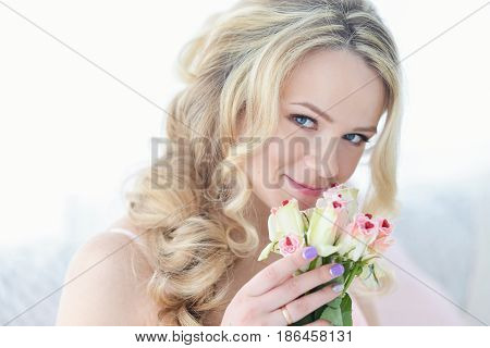 Young happy smiling cheerful woman with bouquet of white roses