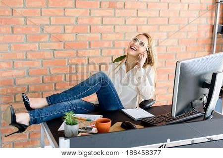 Euphoria. Attractive positive businesswoman smiling while talking on smart phone. She sitting on chair and putting her legs on table against brick wall