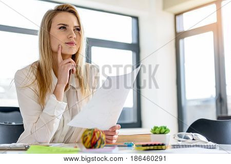 Mull over it. Pleasant charming woman sitting at the table and thinking while holding sheet of paper. She is looking aside dreamily