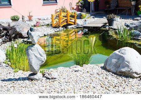 Garden pond with bridge, grass, green, rock