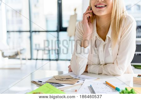 What is new. Smiling businesswoman sitting at table and talking on phone. Window in the background