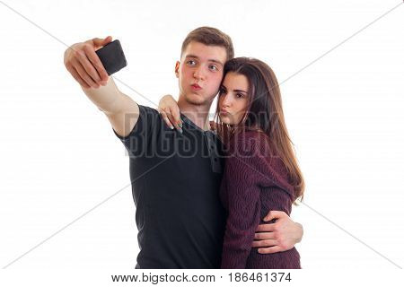 young guy and his cute girl make pics on phone isolated on white background