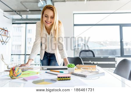 Cheerful leader. Attractive young woman leaning on table with joy. She is looking at her notes with charming smile