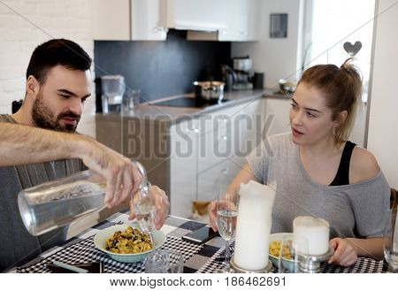 Young couple sitting at the table and eating dinner