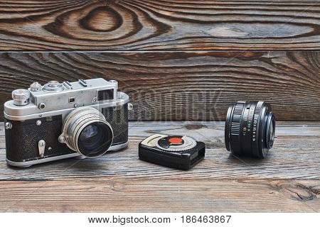 Vintage old retro 35mm rangefinder camera, lens and light meter on wooden background with copy space