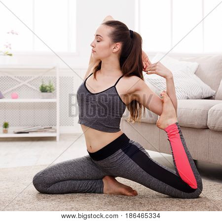 Yoga at home. Woman in mermaid pose. Young slim girl makes exercise near sofa