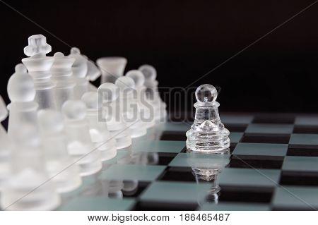 One pawn in front of the opponent's pieces. Minimal business concept. Glass chess on a black background.