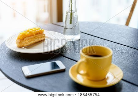 Tasty breakfast. Close-up of sweet pie with hot espresso in yellow cup and vase with flower on black wooden table. Focus on appetizing cake