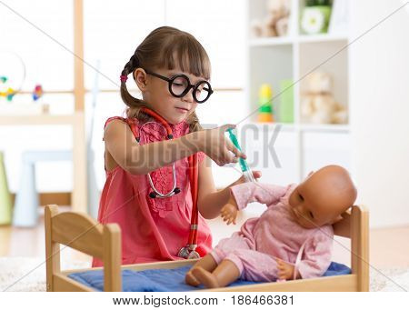kid girl playing a doctor with doll in kindergarten or at home