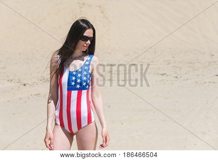 Patriot beautiful woman walking on the beach in July.
