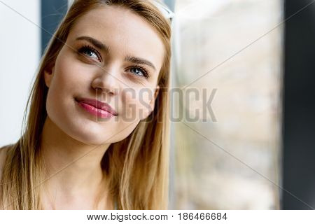 Dreamful beauty. portrait of attractive young woman against big window. She looking aside with slight smile