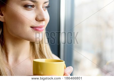 Lost in thoughts. Close-up of attractive lady enjoying morning espresso. She looking through window thoughtfully. Copy space in the right side