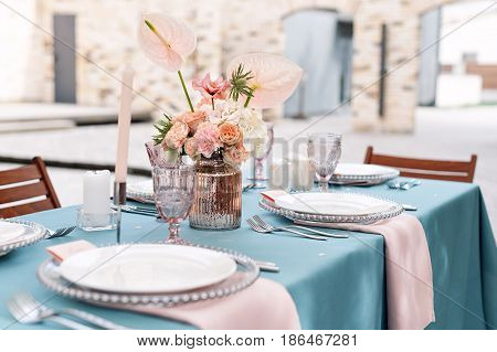 Flower table decorations for holidays and wedding dinner. Table set for holiday, event, party or wedding reception in outdoor restaurant