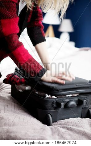 Woman struggling to close suitcase