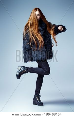 Fashion shot. Full length portrait of a fashionable model with beautiful long hair posing at studio in black fur coat.