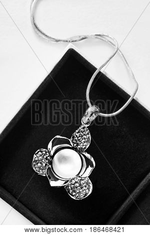 Silver flower pendant with white pearl in jewel box closeup