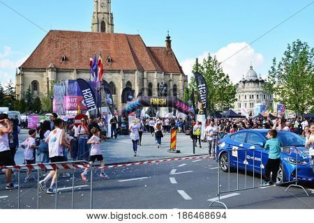 CLUJ-NAPOCA ROMANIA - May 14 2017: Color Run runners reach the finish line in the center of the town. St. Michael's Roman Catholic church in the background.