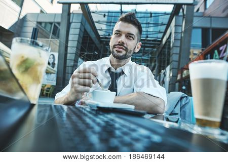 Businessman in cafe terrace outdoors in front of office building, wide and low angle view.