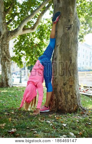 Woman stretching outdoors at citypark by tree in colorful sportswear.