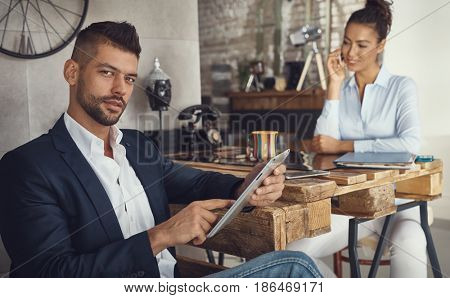 Handsome businessman sitting at stylish office, using tablet.