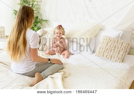 Shy little girl is covering her naked body while looking at camera. Baby is sitting on bed near her mom