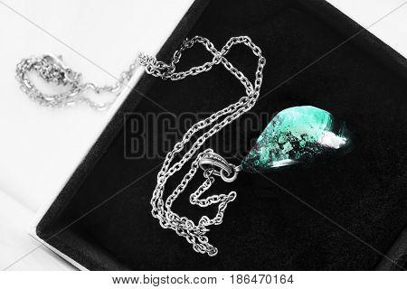 Blue aquamarine pendant in black jewel box closeup