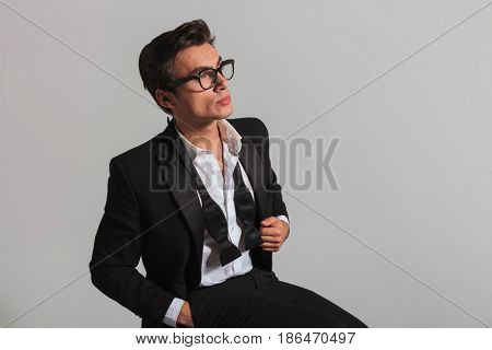 side view of a man in tuxedo and undone bowtie dreaming away on grey background