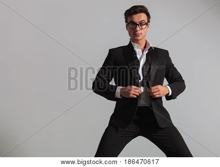 elegant man wearing glasses unbuttoning his tuxedo and looks at the camera on grey background