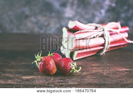 Strawberries and rhubarb on wooden background. Vivid rhubarb. Freshly cut stems of rhubarb and strawberries on a wooden table selective focus Fresh strawberries and rhubarb