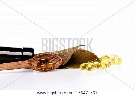 Cod Fish Oil In Omega Capsule In Wooden Spoon