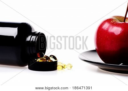 Fish Oil With Vitamin In Black Plastic Jar And Red Apple