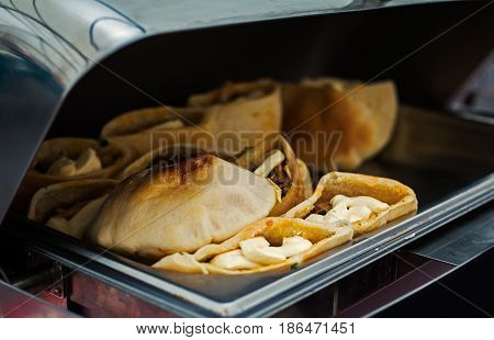 Pitta breads stuffed with vegetables and meat at buffet table