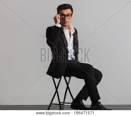 seated elegant man in tuxedo and undone bowtie fixing his glasses in studio