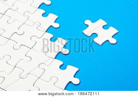 The White jigsaw puzzle on blue background.