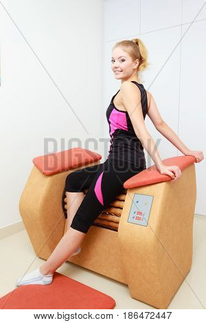 Skincare bodycare wellness concept. Woman getting rid of thighs cellulite on big roll machine. Healthy massage treatment in spa
