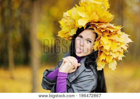 beautiful girl with a wreath of yellow leaves on the head on a background of autumn forest