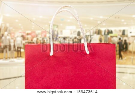 red shopping bag on over blurred mall background.