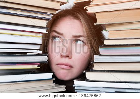 Beautiful Girl Looks Up, Puzzled, Looking Out From Behind The Stacks Of Books. Prepare For An Import