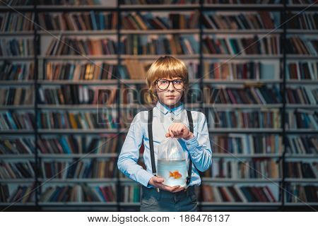 Child with goldfish in library