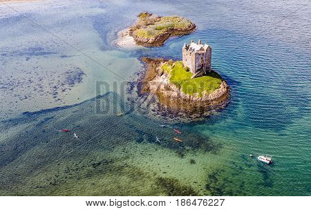 Aerial canoes gathering around the historic castle Stalker in Argyll, Scotland