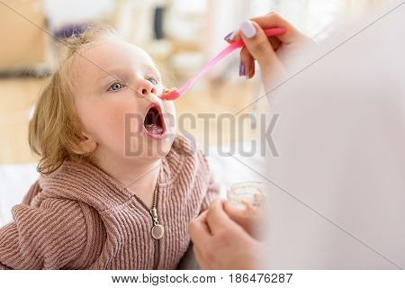 Hungry baby is opening her mouth widely while her mother is giving porridge to her. Portrait