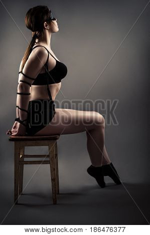 elegant woman with tied hands sitting on chair with closed eyes